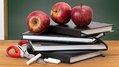 Stock photo of books, apples, scissors and chalk